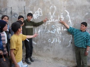 Palestinian kids in Amman point to graffitti mourning the death of 12-year-old Mohammed Dura, HRH April 11, 2002